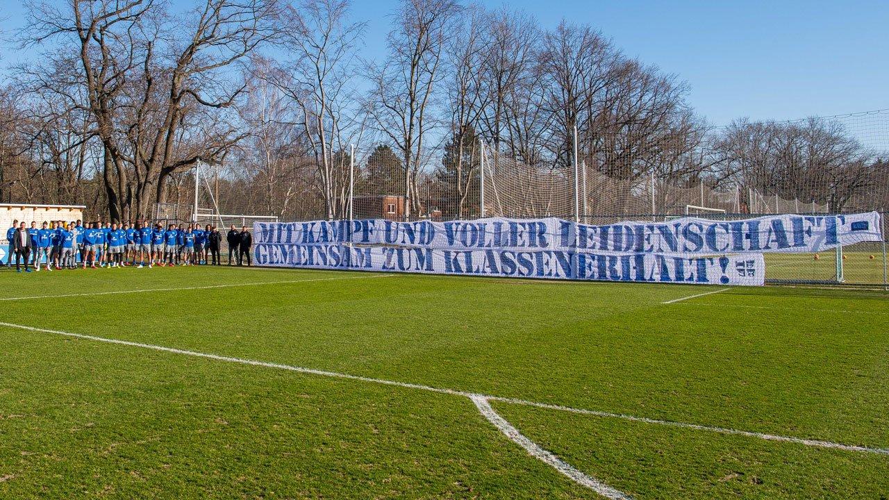 Los jugadores del Hertha frente a la pancarta de los aficionados en Schenckendorffplatz