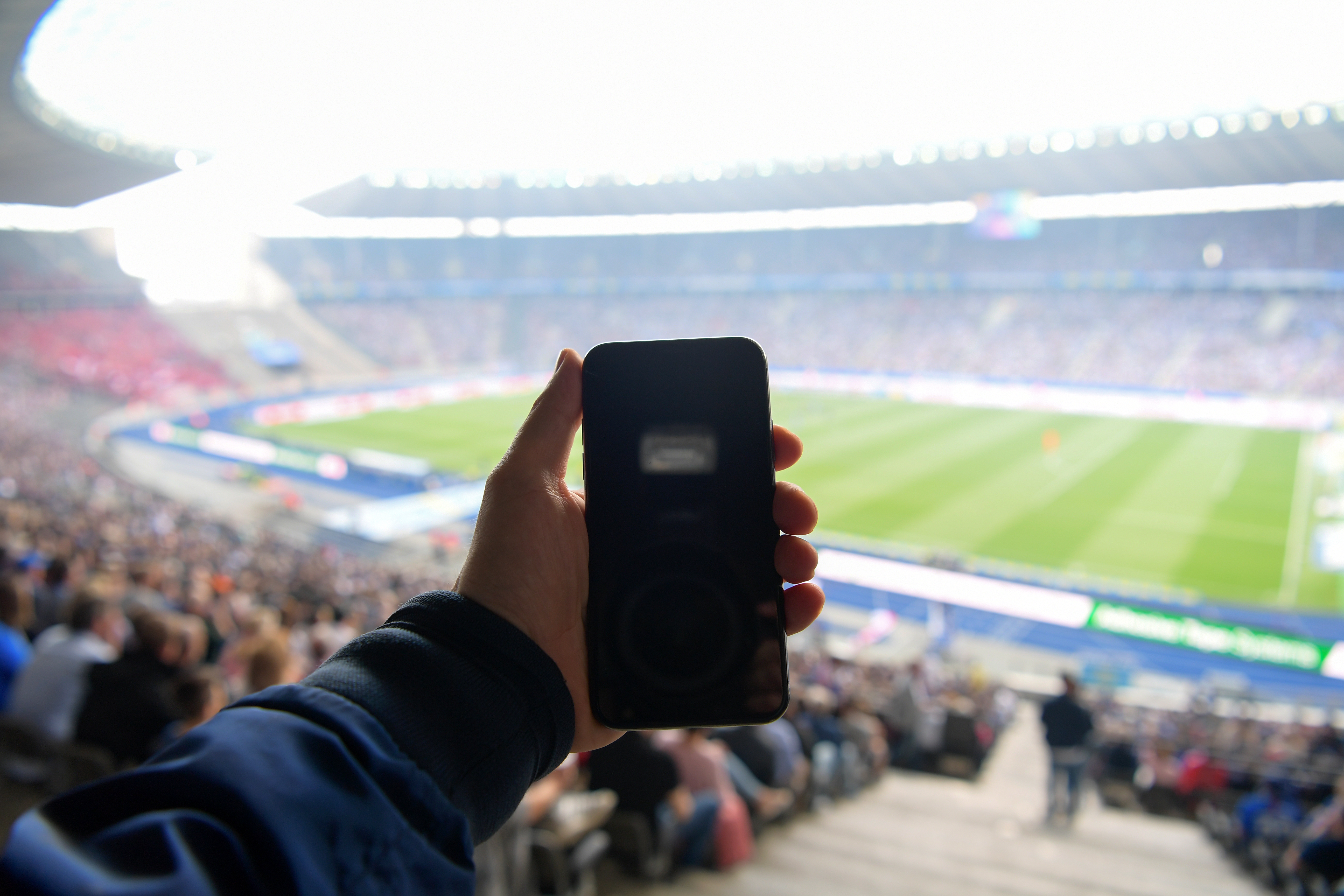 A phone being held up inside the Olympiastadion