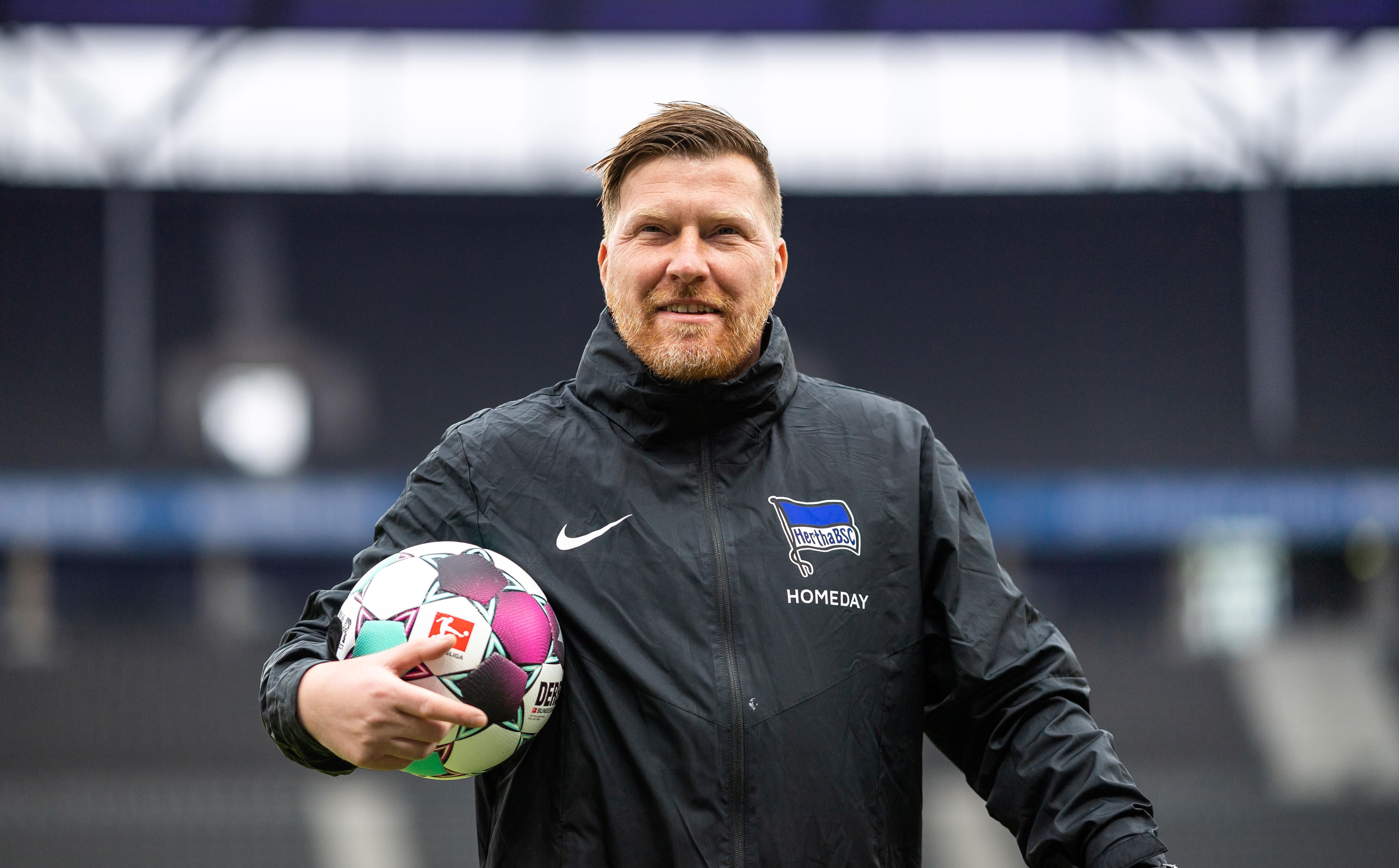 'Zecke' Neuendorf steht im Olympiastadion und hält einen Ball in seinem Arm.