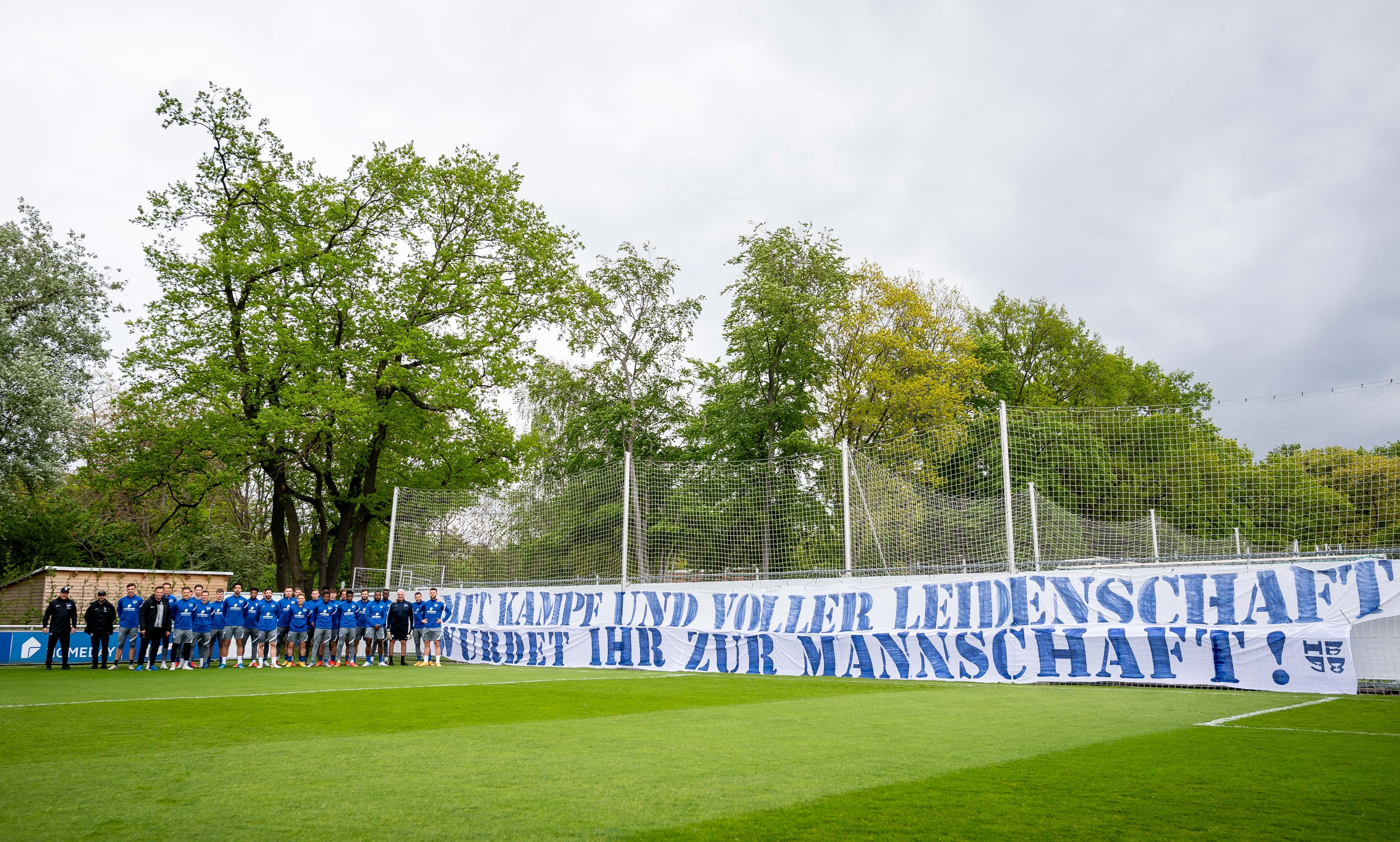 El equipo junto a la pancarta de los fans