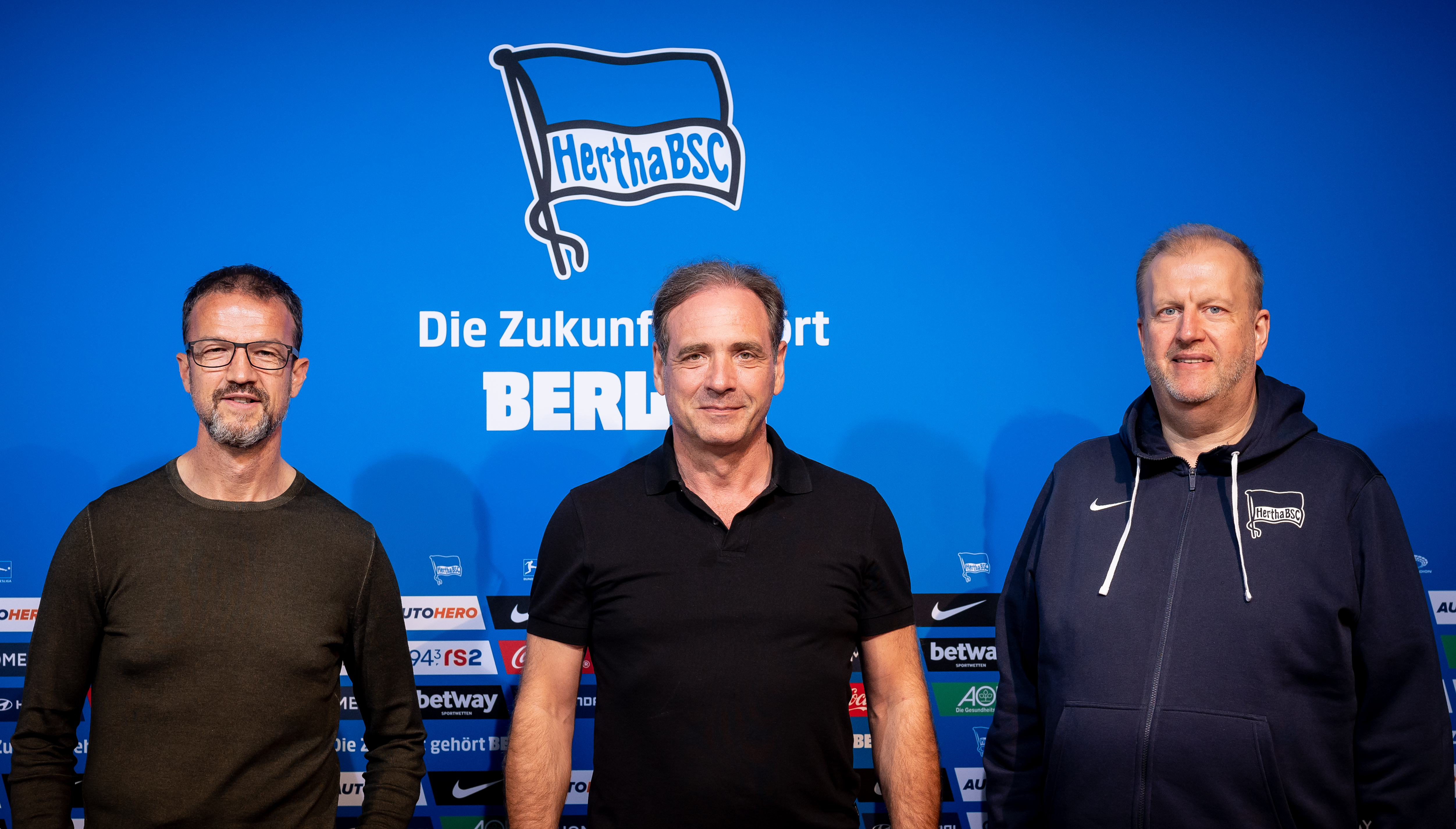 Fredi Bobic, Carsten Schmidt and Ingo Schiller standing in front of the Hertha badge.