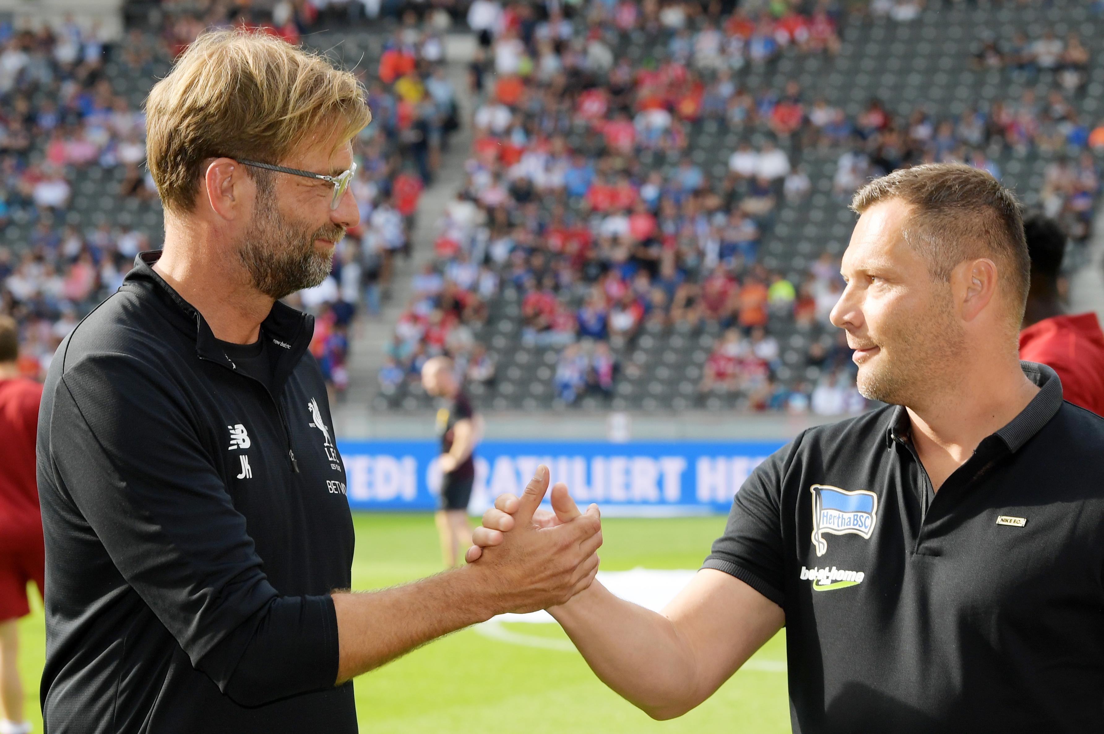 Jürgen Klopp (izq.) y Pál Dárdai (dcha.) saludándose.