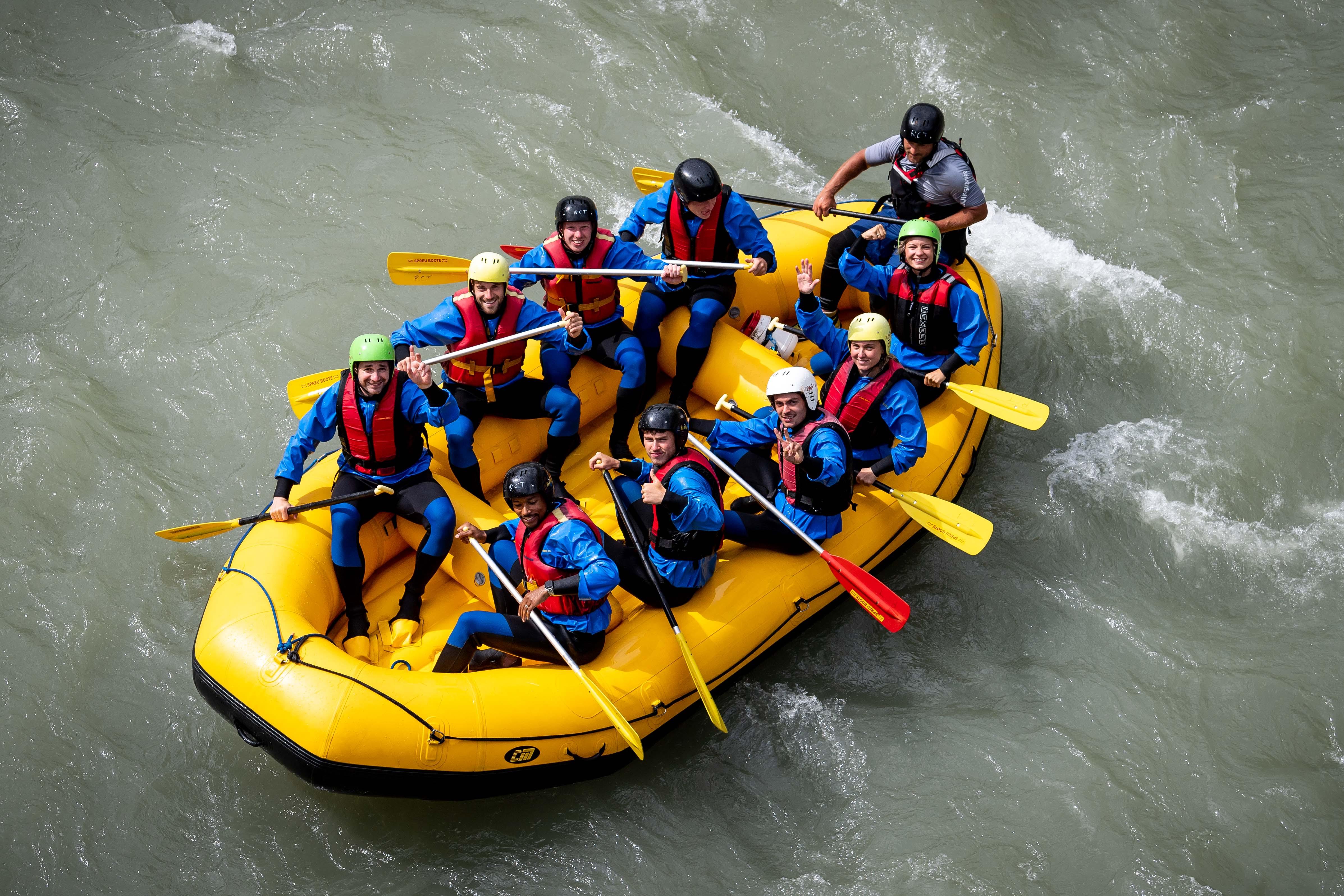 Ein vollbesetztes Schlauchboot mit Spielern und Trainern auf dem Wasser.