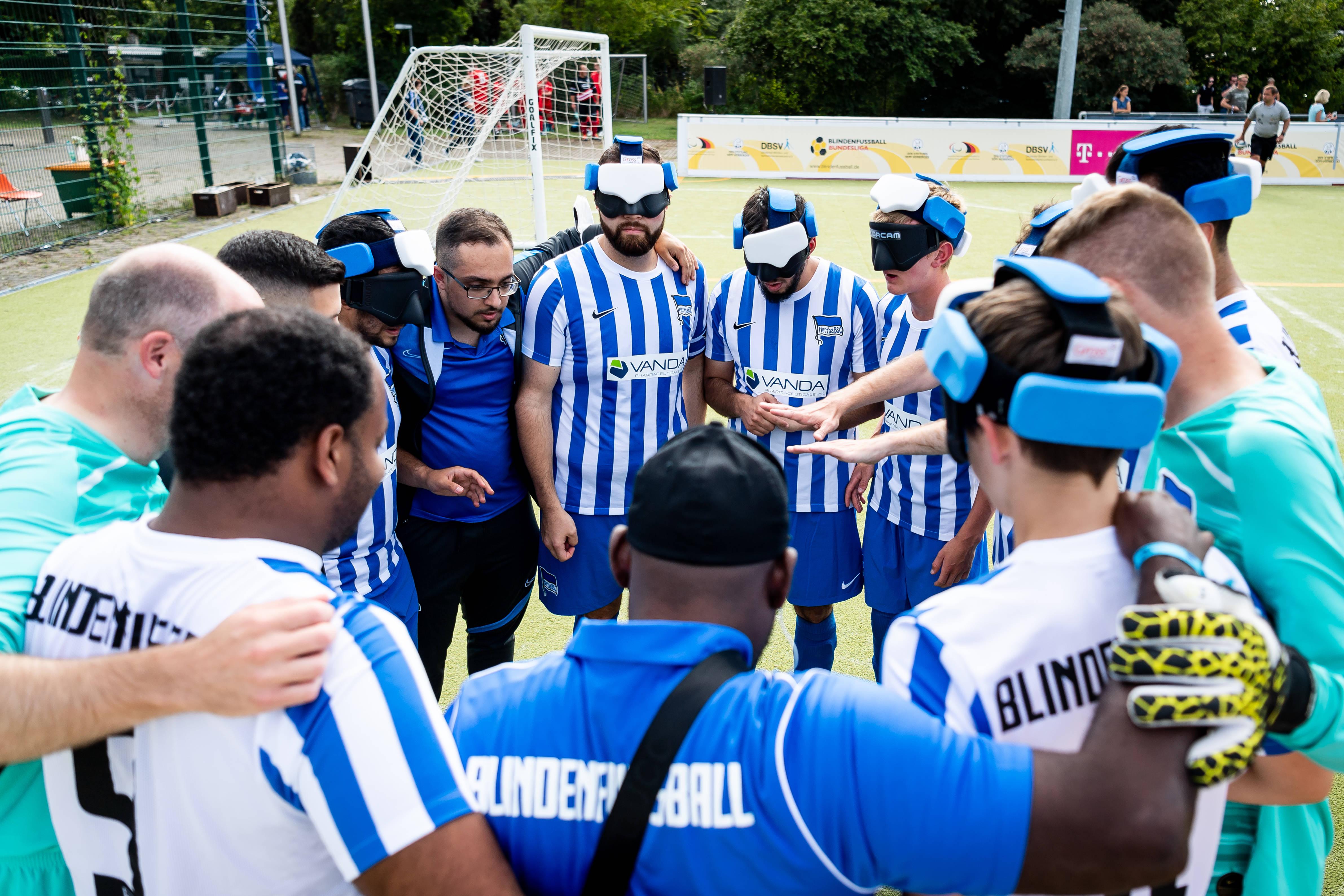 Unsere Blindenfußballer bilden einen Mannschaftskreis.