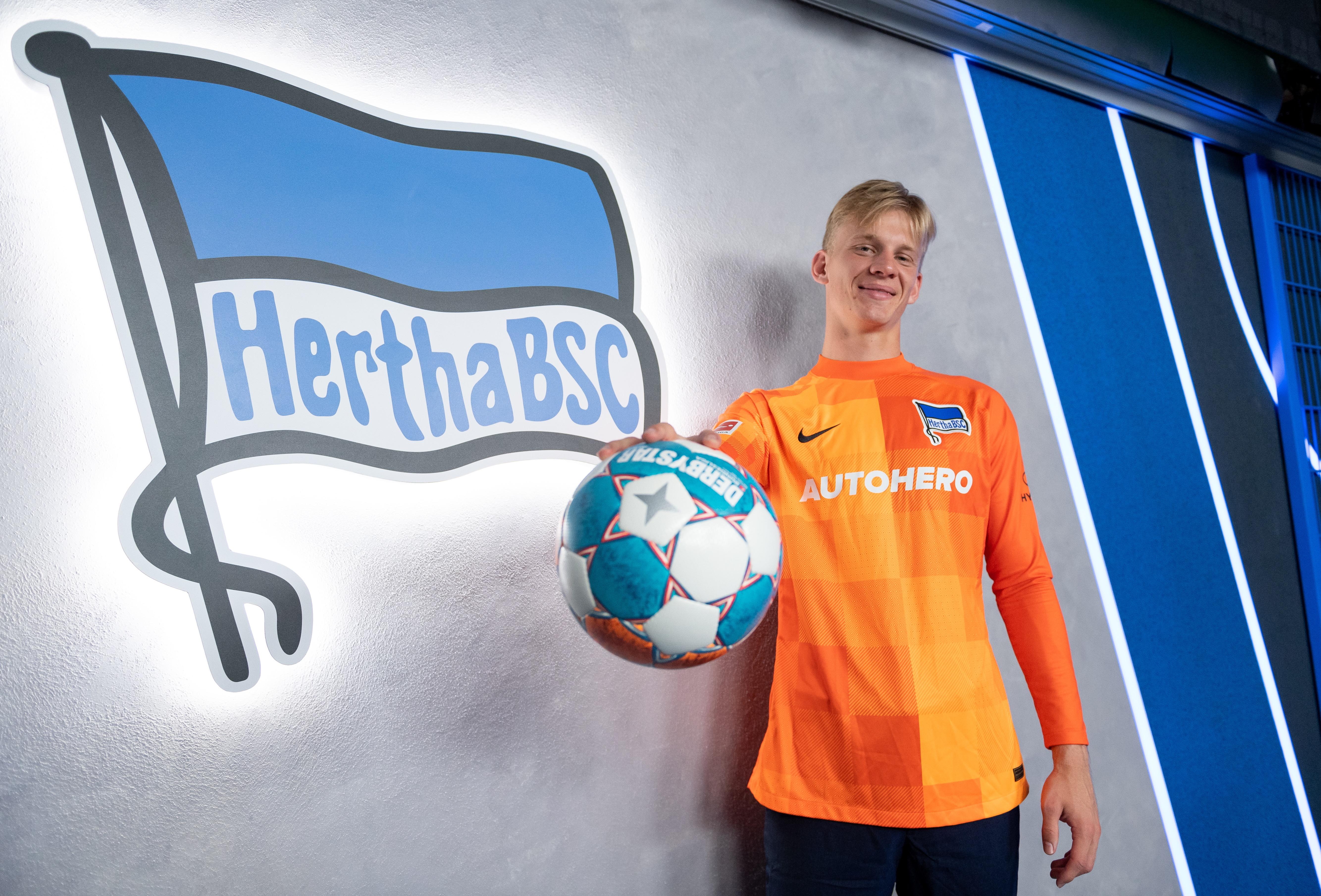 Oliver Christensen con un balón y visitiendo la camiseta del Hertha.