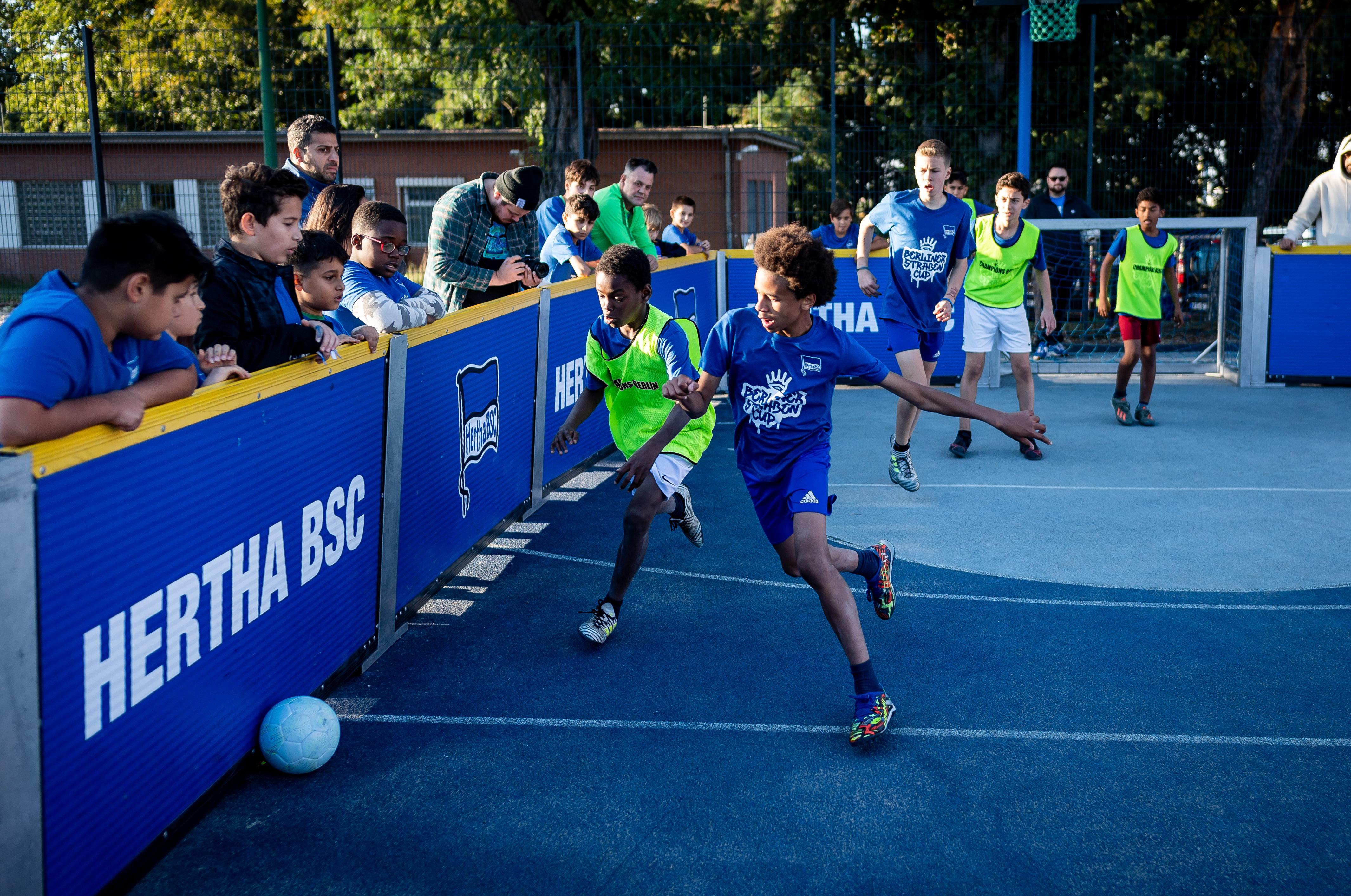 Zwei Jungen kämpfen um den Ball. Die Zuschauer fiebern beim Berliner Straßen Cup von der Bande aus mit.
